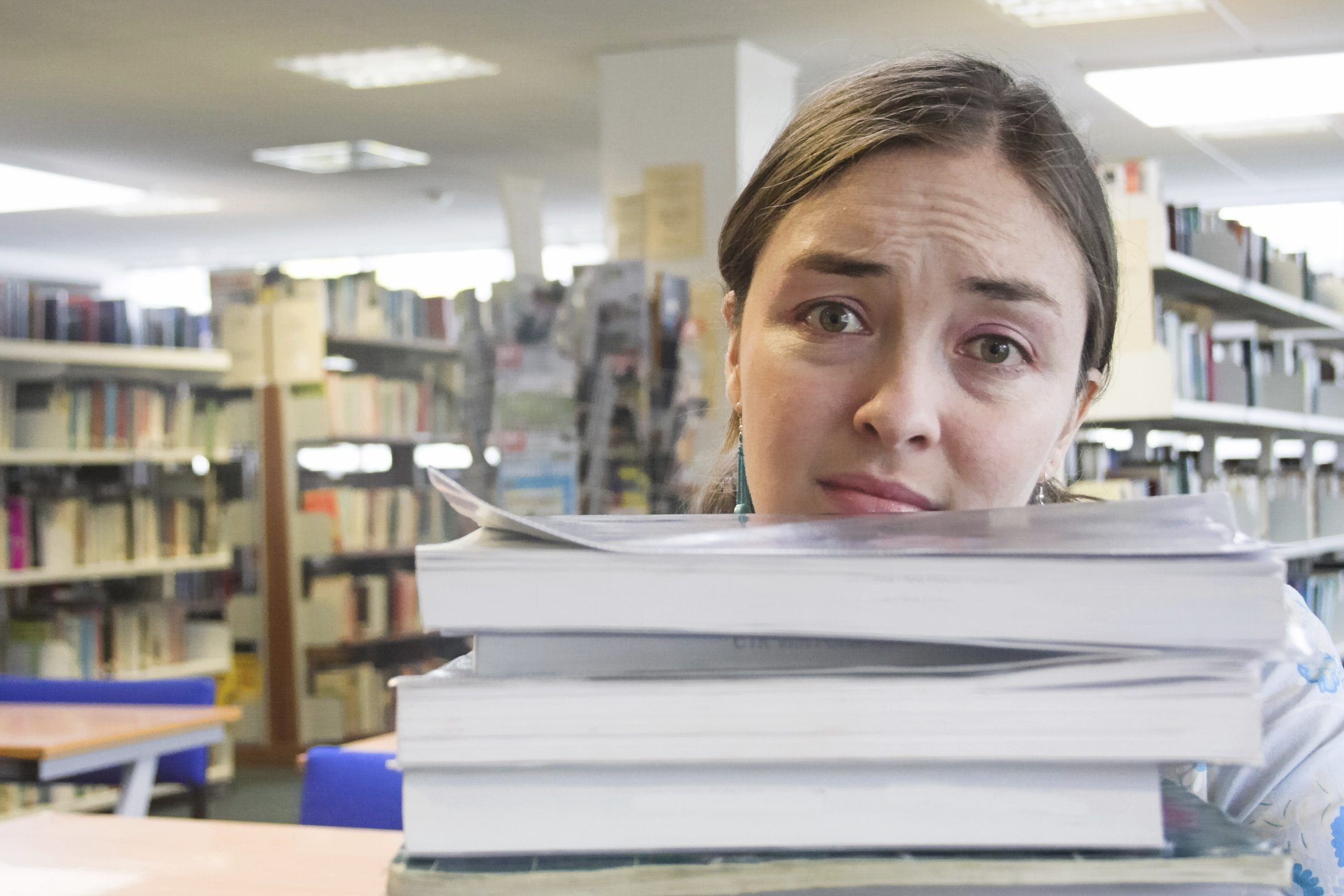 female student in a library with lots of work to do