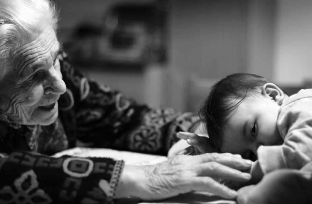 A black and white photo of an older woman reaches out to touch a baby
