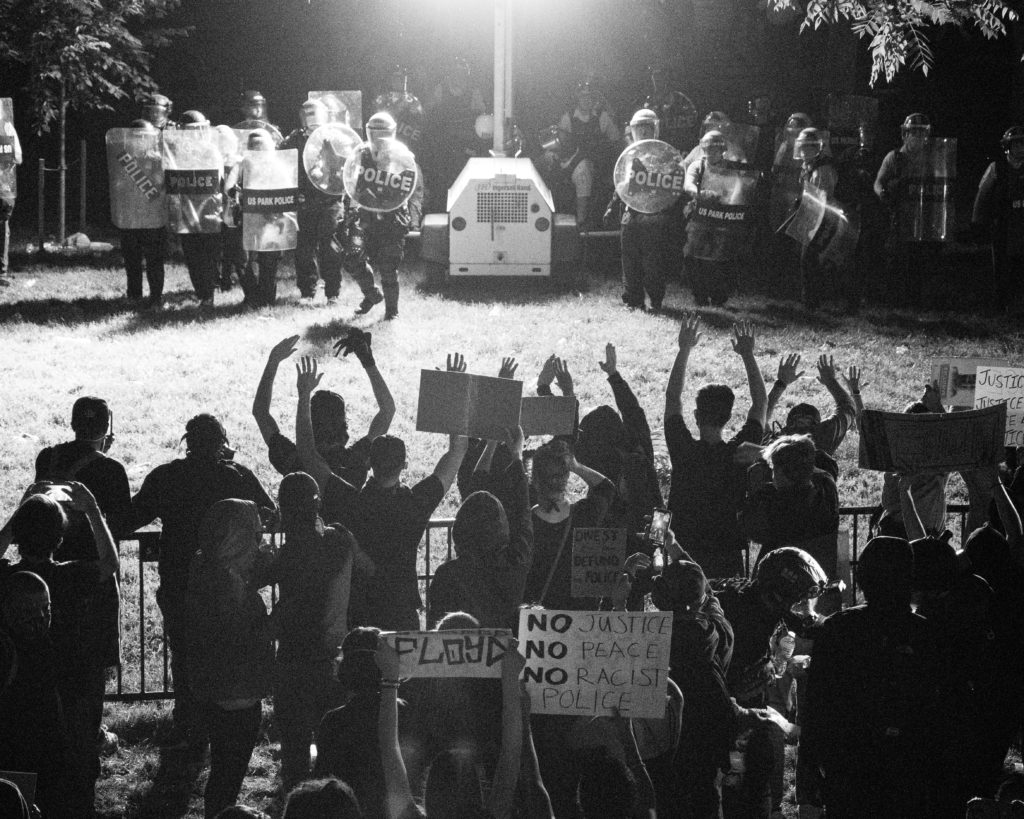 A black and white photo of Black Lives Matters protestors from behind with their hands up as police officers stare them down in riot gear